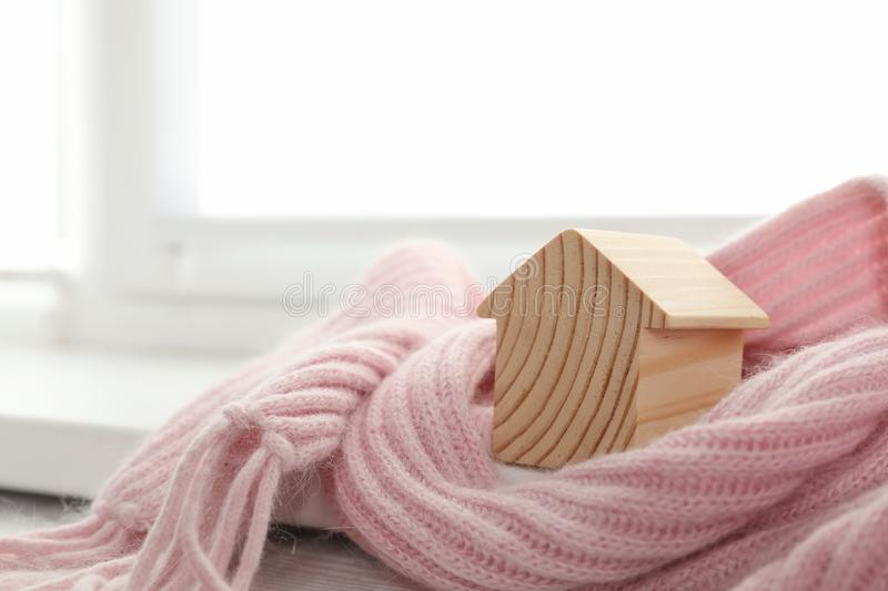 Wooden house model wrapped in pink scarf on  indoors, space for text. Heating efficiency. Wooden house model wrapped in pink scarf on windowsill indoors, space stock image