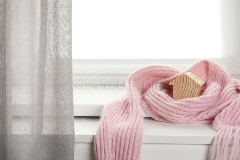 Wooden house model wrapped in pink scarf on windowsill indoors. Heating efficiency. Wooden house model wrapped in pink scarf on windowsill indoors, space for royalty free stock image