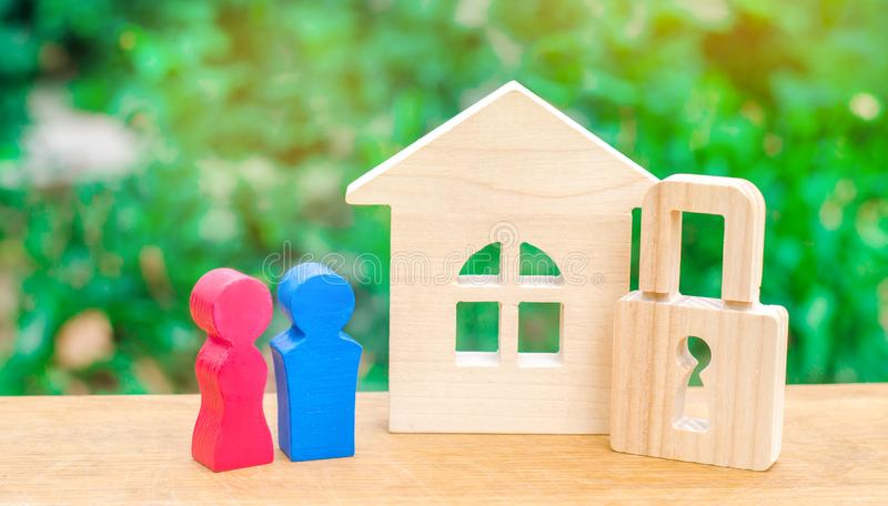 A wooden house with a padlock and a young pair of lovers. The concept of security and tranquility. Stability and confidence royalty free stock images