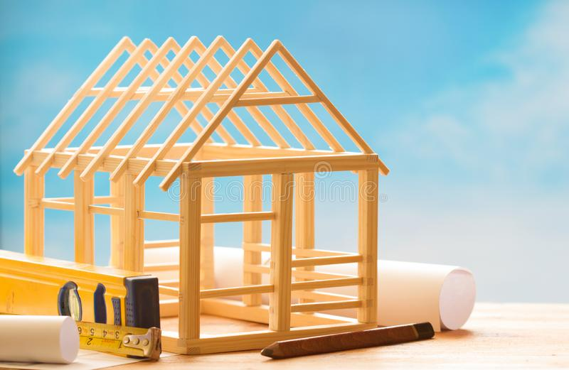 Wooden house and planning on blue sky  construction architecture abstract background concept. Closeup royalty free stock photo