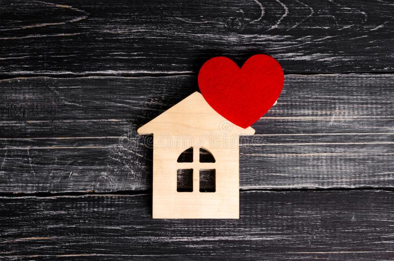 Wooden house with a red heart on a background of black wooden boards. A notification icon for the application. Love nest, love stock photos