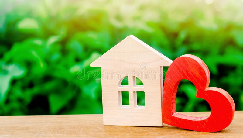 Wooden house and red heart. Concept of sweet home. Property insurance. Family comfort. Affordable housing for young families. royalty free stock photography