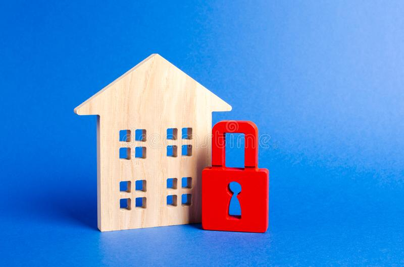 Wooden house and a red padlock. Security and safety. Confiscation for debts. alarm system. seizure of property. Protection of property rights. Unavailable and stock photo