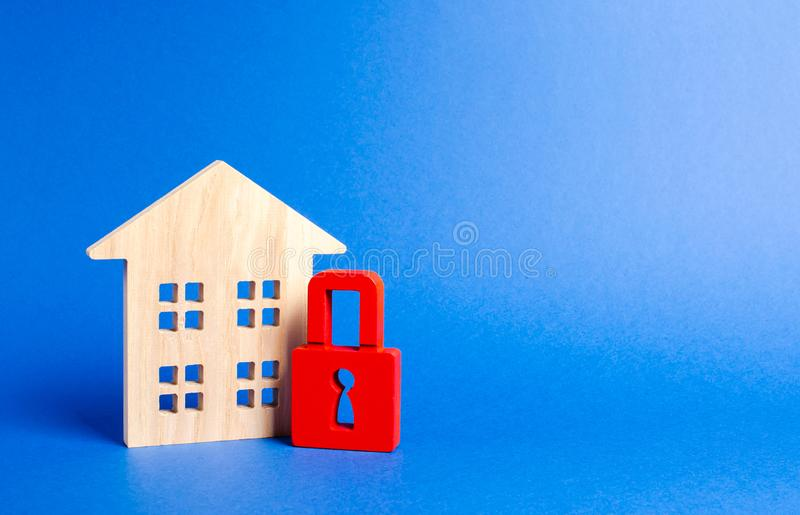 Wooden house and a red padlock. Security and safety. Unavailable and expensive real estate. house Insurance Confiscation for debts. Alarm system. seizure of royalty free stock photography