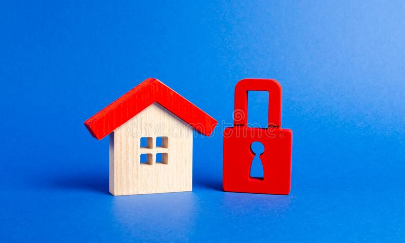 A wooden house and a red padlock. Unavailable and expensive real estate. house Insurance. Security and safety. Confiscation. For debts. alarm system. seizure of royalty free stock photos