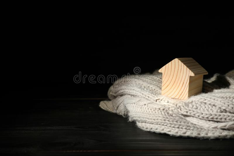 Wooden house  and scarf on table against black background, space for text. Heating efficiency. Wooden house model and scarf on table against black background royalty free stock photos