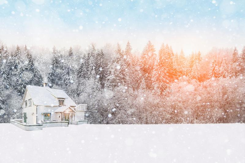 Wooden house with snow on the roof in the background of the forest. royalty free stock photos