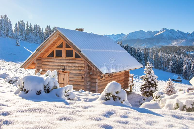 Wooden house in snowy mountains on sunny clear day. European village in Alps in skiing season. Winter nature landscape of snowy royalty free stock images