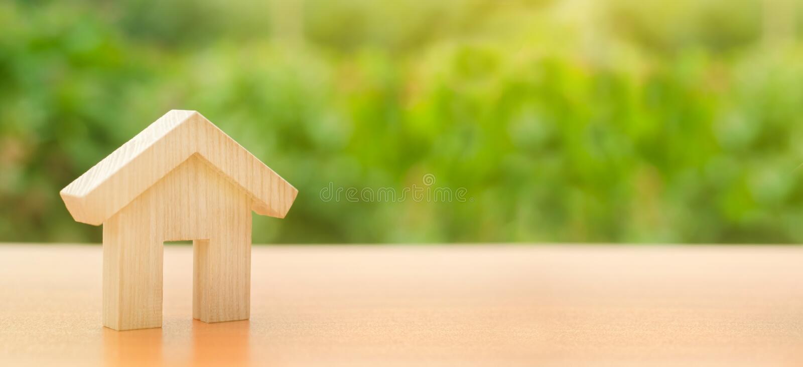 A wooden house stands on a nature green background. Affordable housing, credit and loans. The concept of buying and selling real. Estate, renting. Search for a stock photos