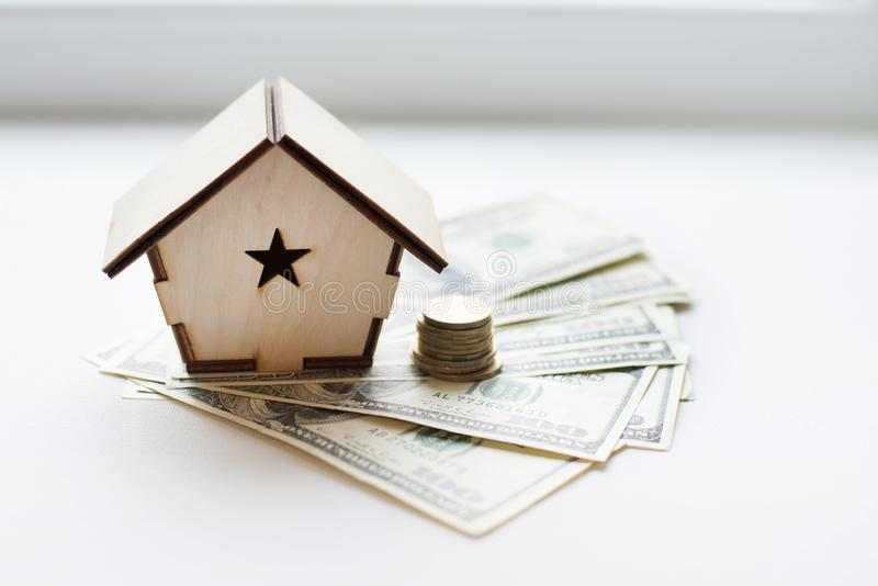 Wooden house stands on a pile of paper bills dollars as a symbol of mortgage on white background. Saving money. Home loan, mortgage, a property investment for royalty free stock image