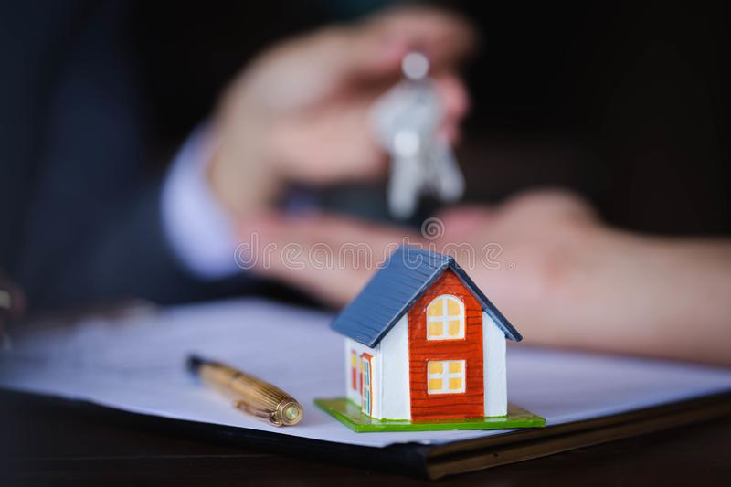 Wooden house on the table background with Real-estate agent giving keys to new property owners after signing contract for realty royalty free stock images