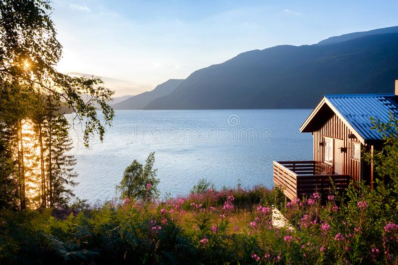 Wooden house with terrace overlooking scenic lake at sunset in N stock photos