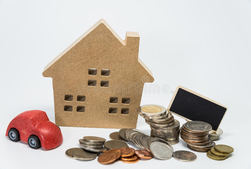 Wooden house toy, red car, small black board and Thai baht coin with white background and selective focus stock photography