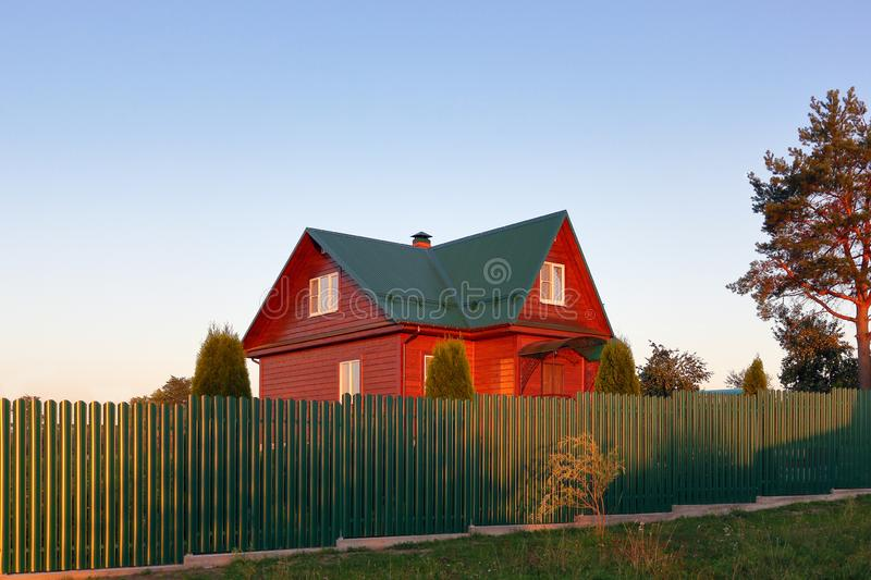 Wooden house under green metal roof house behind the green fence sunset lihgts stock photos