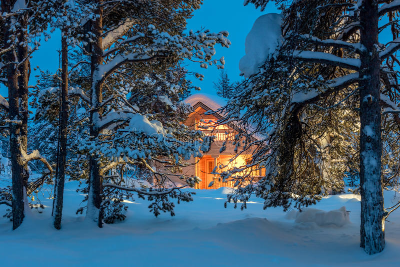 Wooden house with warm light in dark cold winter forest stock image