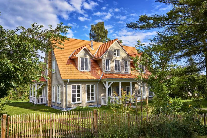 Wooden house with wooden fence on the island Hiddensee. Home, holiday, timber, tree, cottage, summer, building, architecture, blue, europe, nature, travel royalty free stock photos