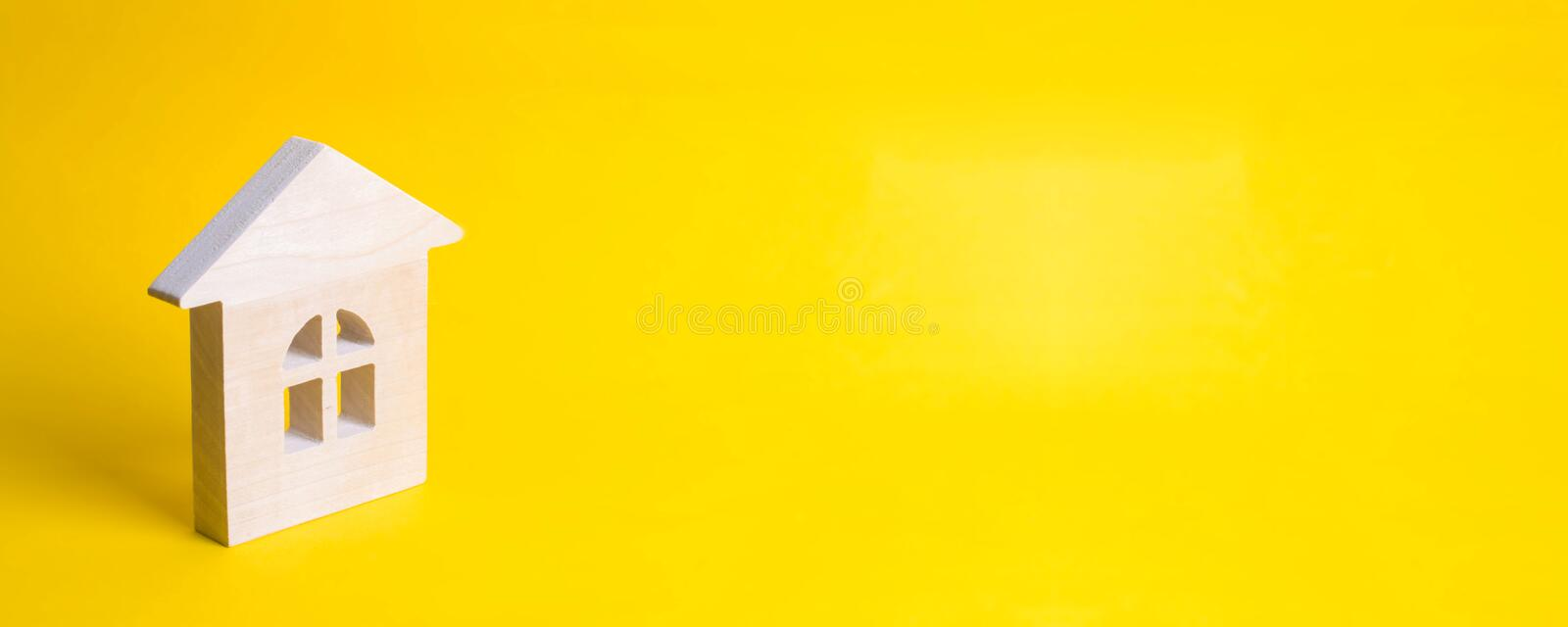 Wooden house on a yellow background. Concept of buying and selling housing, building a house. Rent of apartments. Realtors. stock image