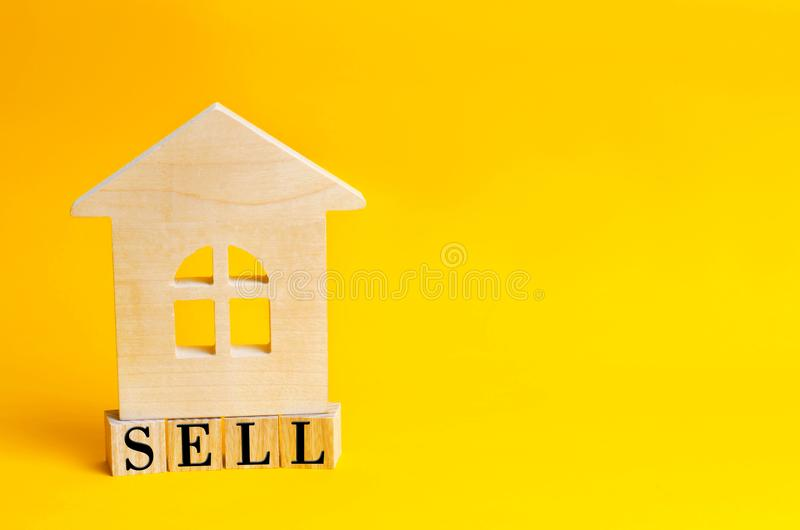 Wooden house on a yellow background with the inscription sell. sale of property, home, real estate. affordable housing. place for. Text. copyspace stock photo