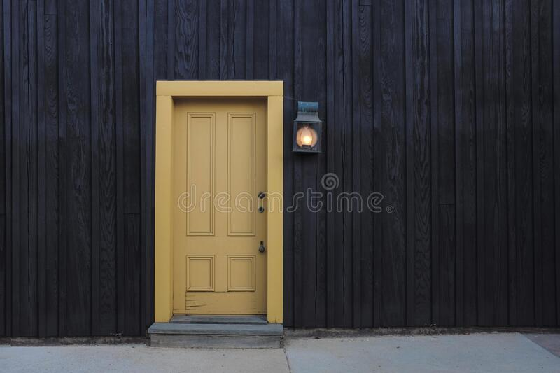 Wooden house with yellow door stock images