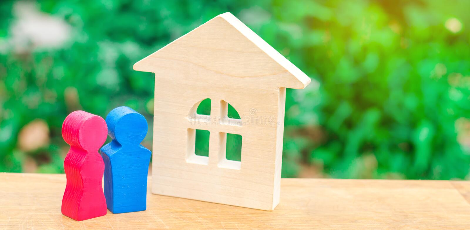 Wooden house and a young pair of lovers. Affordable housing for newlyweds. Stability and confidence in the future. Home alarm stock photo