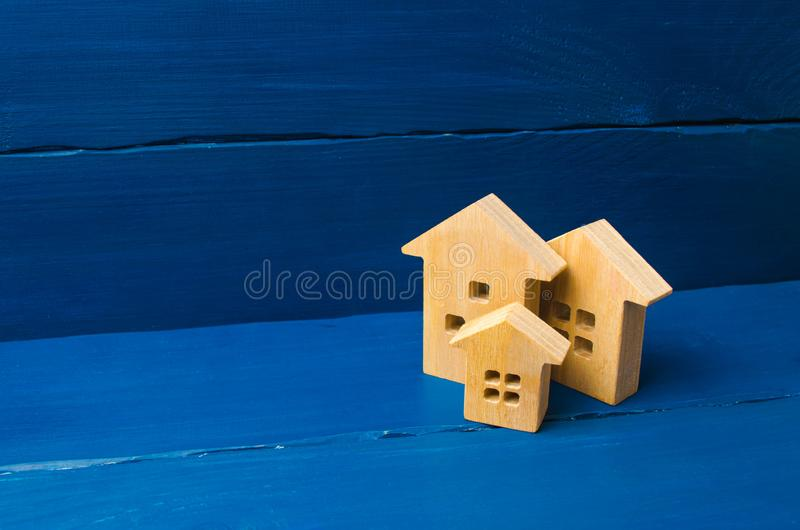 Wooden houses on a blue background. The concept of housing and real estate. Buying and buying a home, selling and investing. Urban growth, urbanization stock photos