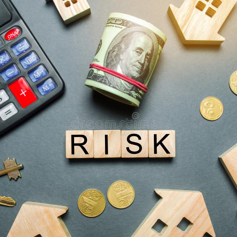 Wooden houses, a calculator, keys, coins and blocks with the word Risk. The risks of investing in real estate. The concept of. Mortgage risk. Loss of property stock photography