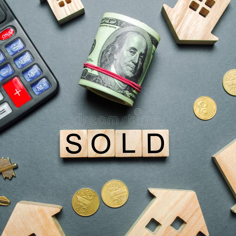 Wooden houses, a calculator, keys, coins and blocks with the word Sold. Concept of selling a house, apartment. Market of real estate. Trade of property royalty free stock photos