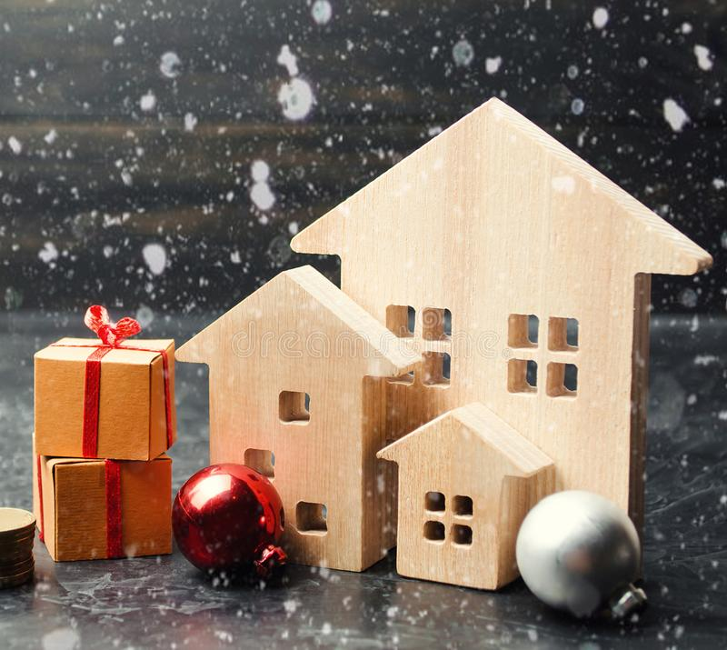 Wooden houses and gifts. Christmas Sale of Real Estate. New Year discounts for buying housing. Purchase apartments at a low price royalty free stock images
