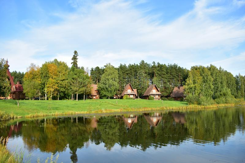 Wooden houses with patterns natural lake, birch grove, pine forest, river, in the sun water royalty free stock photos