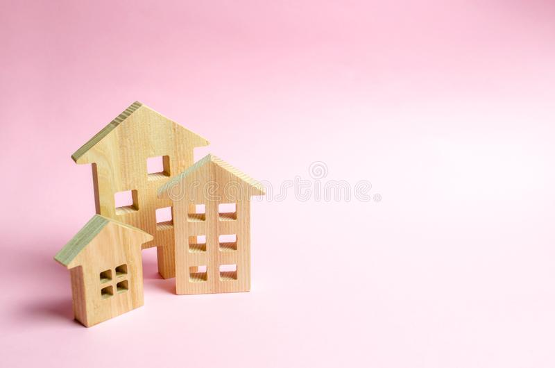 Wooden houses on a pink background. The concept of the city or town. Investing in real estate, buying a house. Management. And business management, market royalty free stock image