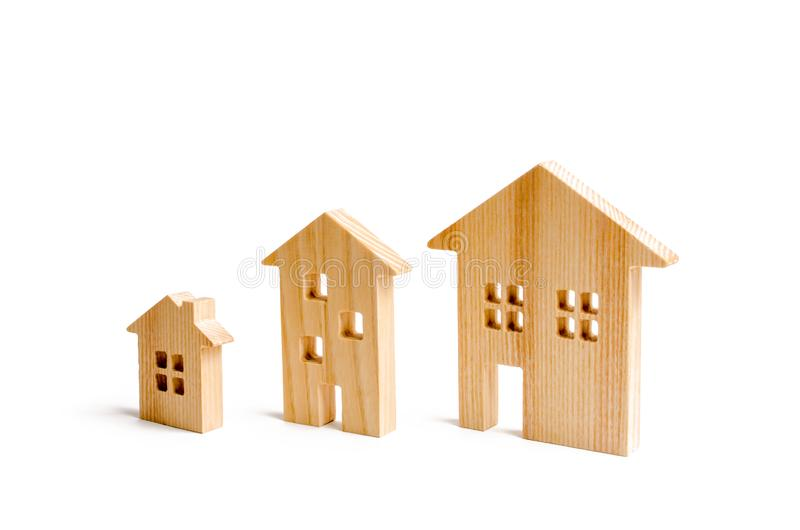 Wooden houses stand in ascending order on a white background. Isolate The concept of increasing population density and high-rise b. Uildings. Agglomeration and stock photos