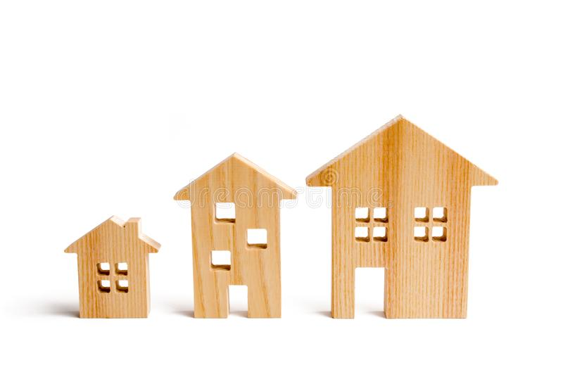 Wooden houses stand in ascending order on a white background. Isolate The concept of increasing population density and high-rise b. Uildings. Agglomeration and stock photo