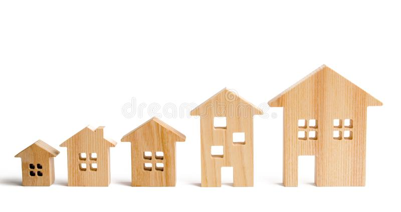 Wooden houses stand in ascending order on a white background. Isolate The concept of increasing population density and high-rise b. Uildings. Agglomeration and stock photography