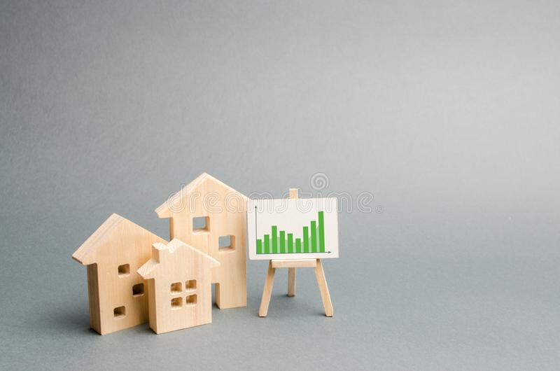 Wooden houses with a stand of graphics and information. Growing demand for housing and real estate. growth of the city and its royalty free stock photos