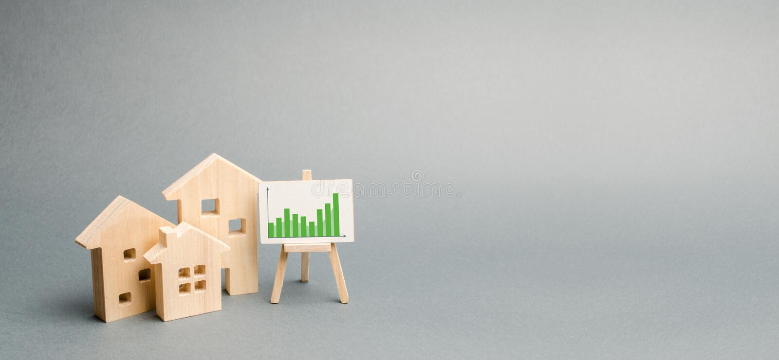 Wooden houses with a stand of graphics and information. Growing demand for housing and real estate. growth of the city. And its population. Investments. banner royalty free stock photos