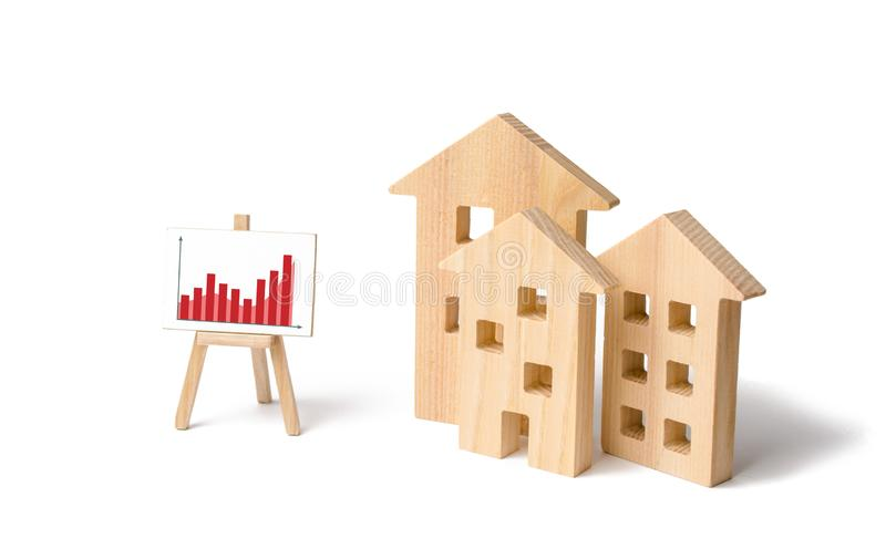 Wooden houses with a stand of graphics and information. Growing demand for housing and real estate. Statistics on the state. Of the market and the number of royalty free stock photo