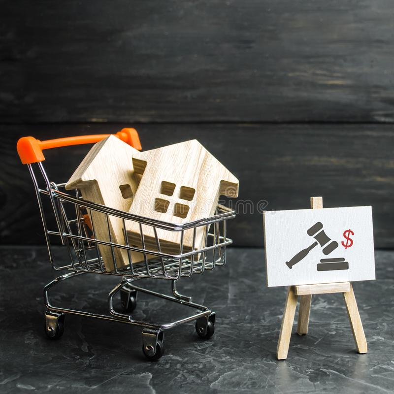 Wooden houses in a supermarket cart. uction for the purchase of housing and buildings. The growth of the city and its population. Investments. concept of stock image
