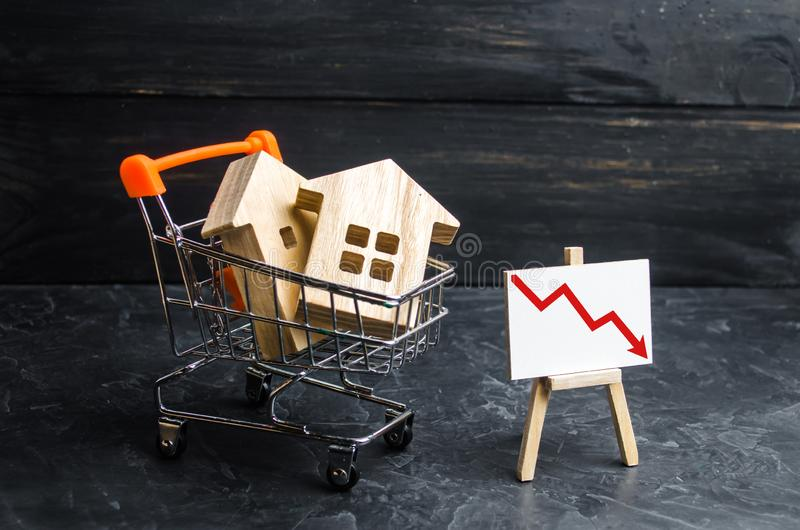 Wooden houses in a supermarket cart and up down. Reduction of demand for housing and real estate. The concept of falling prices stock photography