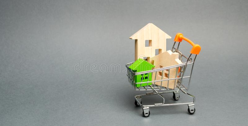 Wooden houses in a Supermarket trolley. The concept of buying a house or apartment. Affordable housing. Profitable and cheap loans stock image