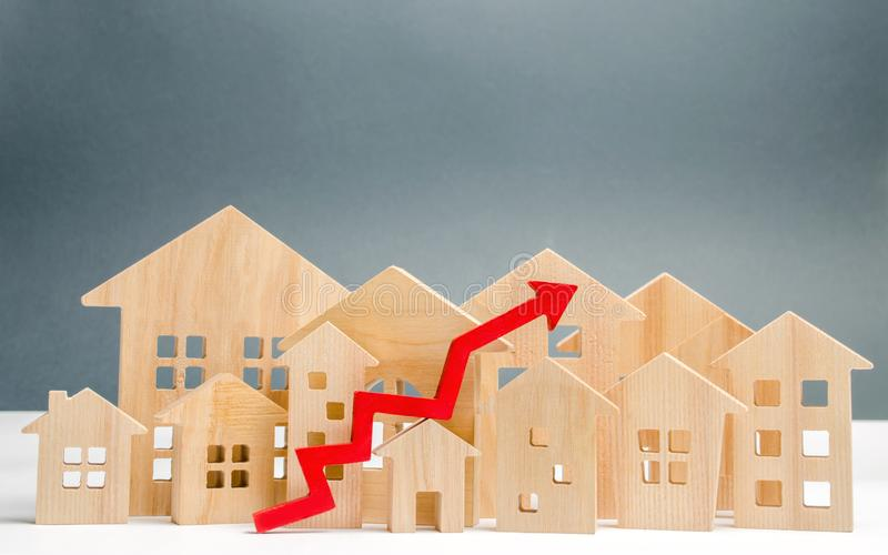 Wooden houses and up arrow. The concept of real estate market growth. The increased in housing prices. Rise price for utilities /. Rent. Increased demand for royalty free stock image