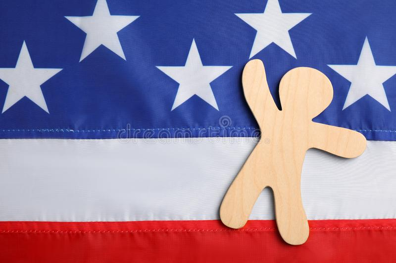 Wooden human figure on national USA flag, top view. royalty free stock image