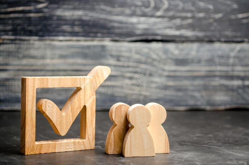 Wooden human figures stand together next to a tick in the box. The concept of elections and social technologies. Volunteers, parti. Es, candidates, constituency stock photo