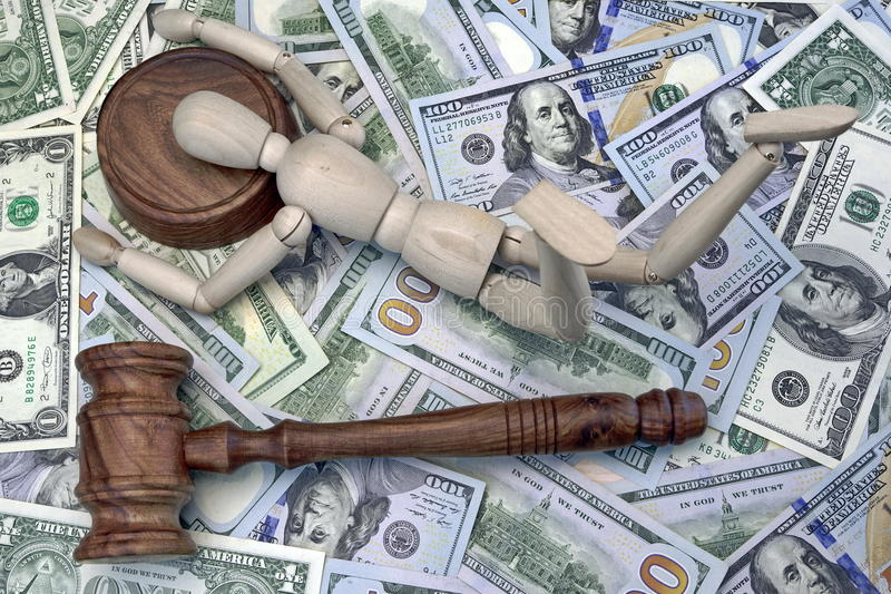 Wooden Human Figurine On The Sound Block And Cash Background. Judges Gavel, Wooden Human Figurine Laying On The Sound Block And Money Dollar Background royalty free stock photos