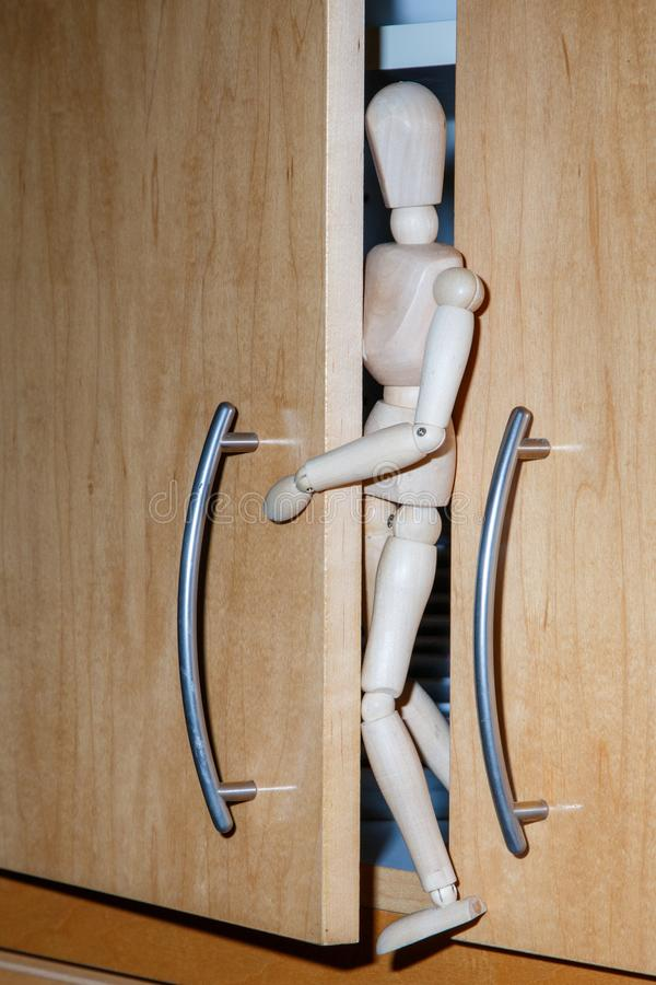 Wooden Human Mannequin Figure Model trying to hide in the closet. Wooden Human Mannequin Figure Model trying to hide in the kitchen closet royalty free stock photography