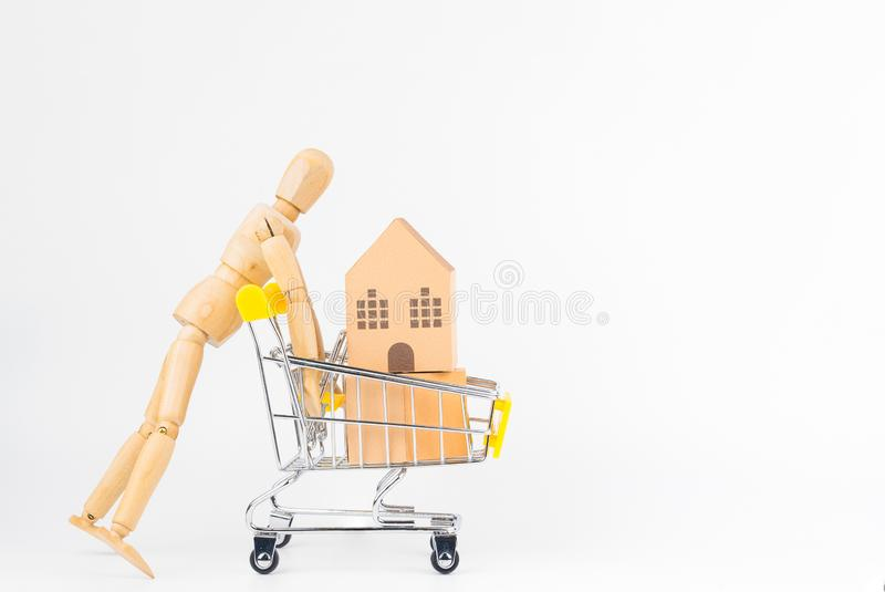 Wooden human mannequin holding shopping cart full of paper hose. Model, isolated on white background with copy space.Real estate concept, New house concept royalty free stock photos