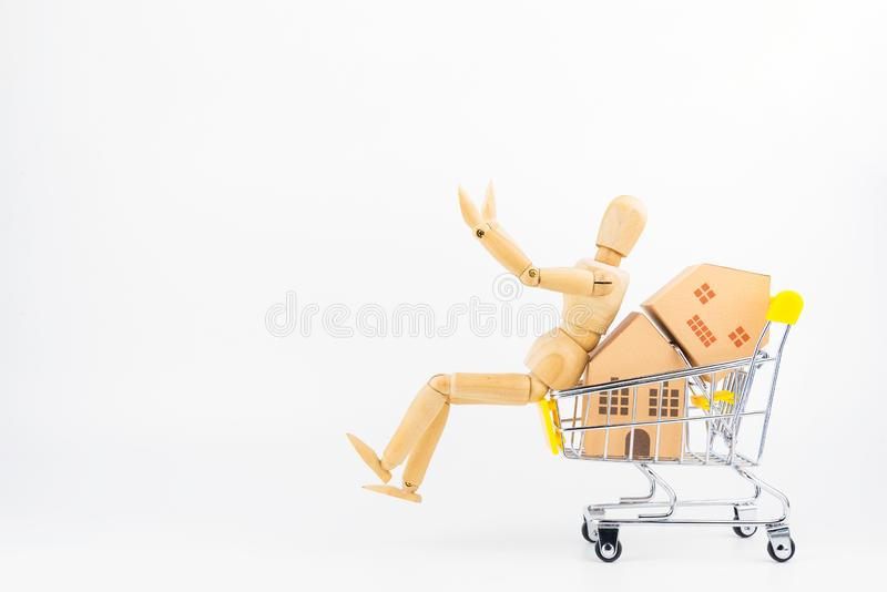 Wooden human mannequin holding shopping cart full of paper hose. Model, isolated on white background with copy space.Real estate concept, New house concept royalty free stock photo