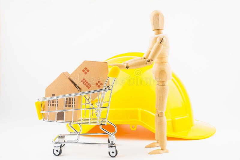 Wooden human mannequin holding shopping cart full of paper hose. Model, isolated on white background with copy space.Real estate concept, New house concept royalty free stock photography