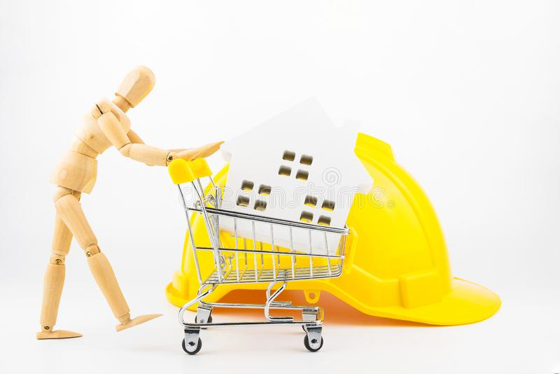 Wooden human mannequin holding shopping cart full of paper hose. Model, isolated on white background with copy space.Real estate concept, New house concept royalty free stock images