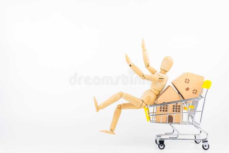Wooden human mannequin holding shopping cart full of paper hose. Model, isolated on white background with copy space.Real estate concept, New house concept stock photography