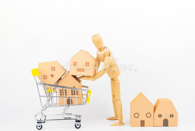 Wooden human mannequin holding shopping cart full of paper hose. Model, isolated on white background with copy space.Real estate concept, New house concept stock photos
